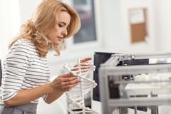 Hübsche Frau, die DNA-Modell gemacht mit Drucker 3D kontrolliert Stockbild