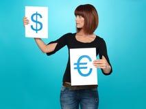 Hübsche Frau, die Dollar und Eurozeichen zeigt Lizenzfreie Stockfotos