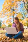Hübsche Frau, die draußen in einem Herbstpark arbeitet Lizenzfreie Stockbilder