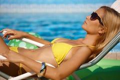Hübsche Frau, die durch Pool ein Sonnenbad nimmt Stockfoto