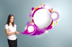 Hübsche Frau, die ein Telefon hält und abstraktes Sprache bubb darstellt Stockfoto