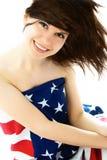 Hübsche Frau, die eine amerikanische Flagge trägt Lizenzfreie Stockfotografie