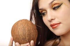 Hübsche Frau, die eine Kokosnuss mustert stockfotos
