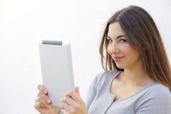 Hübsche Frau, die eine Tablette hält und Kamera betrachtet Stockfotografie