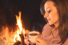 Hübsche Frau, die eine Tasse Tee nahe dem Herd trinkt lizenzfreie stockbilder