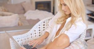 Hübsche Frau, die in einem geflochtenen Stuhl sich entspannt Lizenzfreie Stockfotos
