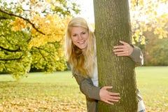Hübsche Frau, die einen Baum huggging ist Stockbild