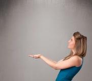 Hübsche Frau, die einen leeren Kopienraum darstellt stockbild