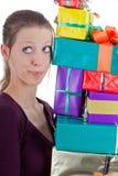 Hübsche Frau, die einen Stapel Geschenke trägt Lizenzfreie Stockfotos