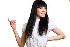 Hübsche Frau, die Finger in Richtung zur Leerstelle zeigt Stockbild