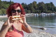 Hübsche Frau, die frisches Meeresfruchtsandwich genießt Stockfotos