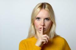 Hübsche Frau, die Geste an der Kamera zum Schweigen bringend darstellt Stockfotografie