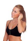 Hübsche Frau, die hörende Musik der Eignung mit Kopfhörern tut stockfotos