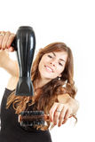 Hübsche Frau, die hairdryer und Haarbürste bei der Arbeit verwendet Lizenzfreie Stockfotografie