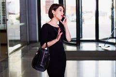 Hübsche Frau, die am Handy geht und spricht Lizenzfreies Stockbild