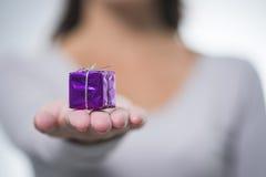 Hübsche Frau, die heraus ein kleines purpurrotes Geschenk hält Stockbilder