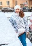 Hübsche Frau, die hinter schneebedecktem Auto steht Lizenzfreies Stockfoto
