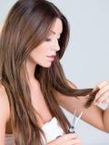 Hübsche Frau, die ihr Haar unter Verwendung der Scheren trimmt Stockfotos