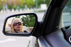 Hübsche Frau, die ihr Kabriolett-Sport-Auto mit ihrem Sunglas fährt Stockfotografie