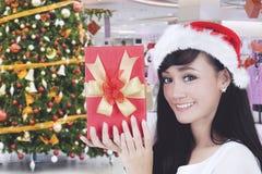 Hübsche Frau, die ihr Weihnachtsgeschenk im Mall zeigt stockfotografie
