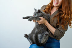 Hübsche Frau, die ihre russische blaue Katze in den Händen hält Lizenzfreie Stockfotos
