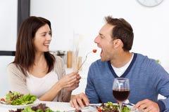 Hübsche Frau, die ihrem Freund eine Tomate gibt lizenzfreie stockbilder