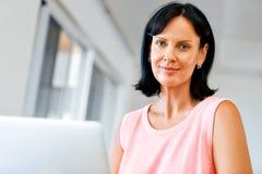 Hübsche Frau, die an ihrem Laptop arbeitet Lizenzfreies Stockbild