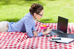 Hübsche Frau, die ihren Laptop im Park verwendet Lizenzfreie Stockfotografie