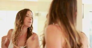 Hübsche Frau, die im Badezimmer sich schaut stock video