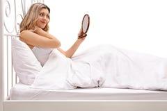 Hübsche Frau, die im Bett liegt und in einem Spiegel schaut Lizenzfreies Stockfoto