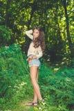 Hübsche Frau, die im Park am sonnigen Sommertag aufwirft Stockbilder