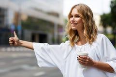 Hübsche Frau, die Kaffee hält und Transport mit dem Daumen oben stoppt Lizenzfreies Stockbild