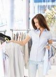 Hübsche Frau, die Kleidung kauft Stockbild