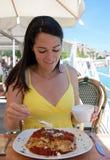 Hübsche Frau, die Lasagne isst Stockfoto