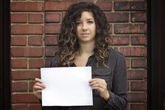 Hübsche Frau, die leeres Zeichen oder Papier hält Stockfotografie