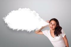 Hübsche Frau, die mit abstraktem Wolkenexemplarplatz gestikuliert Stockfotos