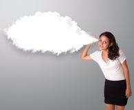 Hübsche Frau, die mit abstraktem Wolkenkopienraum gestikuliert Lizenzfreie Stockfotografie