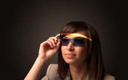 Hübsche Frau, die mit futuristischen High-Techen Gläsern schaut Stockfotos