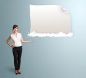 Hübsche Frau, die modernen Kopienraum auf Wolken darstellt Lizenzfreie Stockfotografie