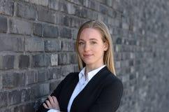 Hübsche Frau, die nahe Backsteinmauer lächelt Lizenzfreie Stockfotos