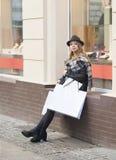 Hübsche Frau, die nahe einem Laden mit Schaufenster stillsteht Lizenzfreies Stockfoto