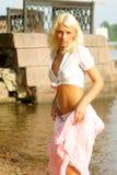 Hübsche Frau, die nahes Wasser steht Stockfotos