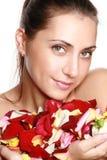 Hübsche Frau, die rosafarbene Blumenblätter anhält Lizenzfreies Stockfoto