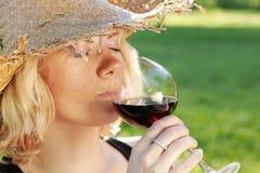 Hübsche Frau, die Rotwein riecht Lizenzfreie Stockfotos
