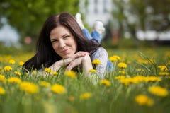 Hübsche Frau, die sich auf Löwenzahnfeld, glückliches nettes gir hinlegt Lizenzfreie Stockfotos