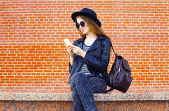 Hübsche Frau, die Smartphone in der Felsenschwarzart über Ziegelsteinen verwendet lizenzfreies stockfoto