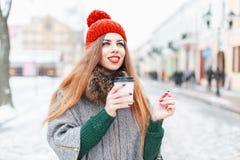 Hübsche Frau, die in die Stadt, ein heißes Getränk im Winter trinkend geht Stockfotos