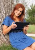 Hübsche Frau, die Tablette verwendet stockbilder
