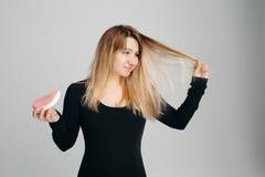 Hübsche Frau, die unordentliches Haar in einer Hand und Haarbürste in einer anderen hält Stockbild