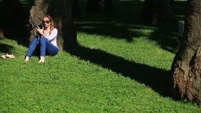 Hübsche Frau, die unter einer Palme sitzt und das Internet auf einem Smartphone grast stock footage